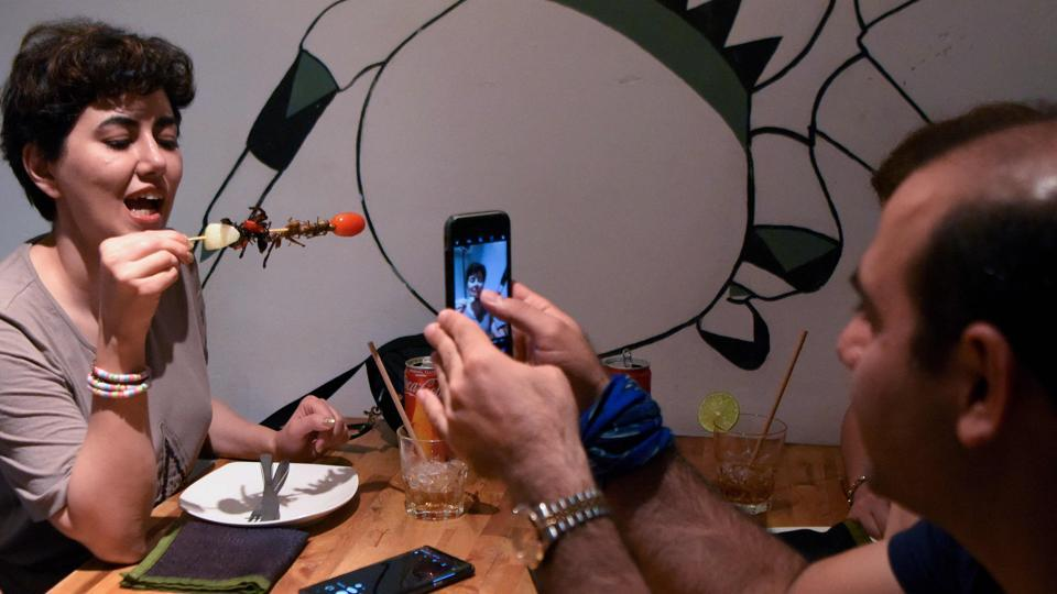 """A tourist (L) holds up skewered cricket and spiders for a picture at the Bugs Cafe restaurant in Siem Reap province, Cambodia. Ant spring rolls, silkworm taro croquettes and a """"bug mac"""" -- Cambodia's first insect tapas restaurant is mixing cocktail culture with creepy crawler fare. (Tang Chhin Sothy / AFP)"""