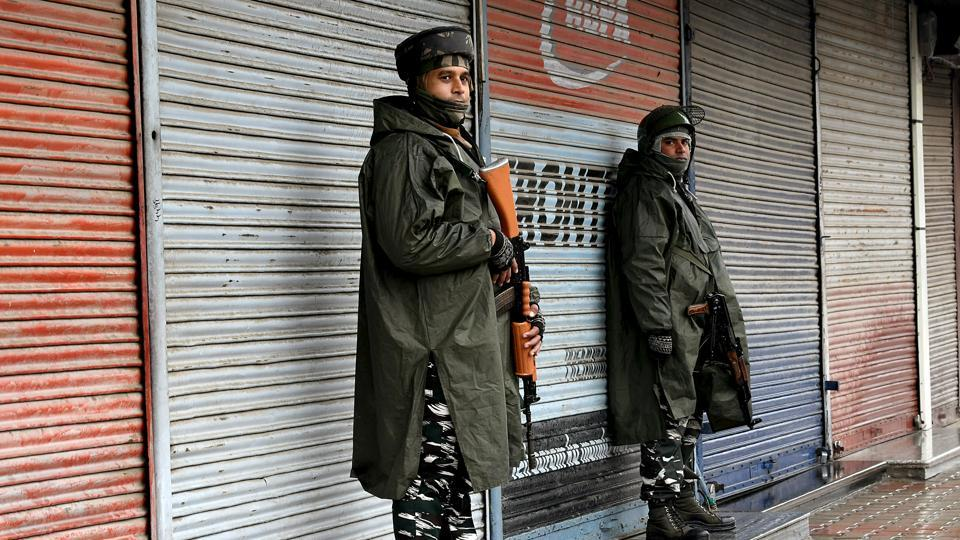 CRPF personnel stand guard in front of a market in Srinagar.