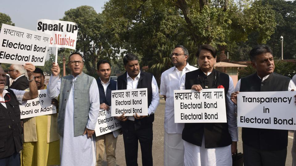 MPs from Congress protest against the lack of transparency in electoral bonds, in front of the Gandhi Statue at the Parliament during the Winter Session in New Delhi.