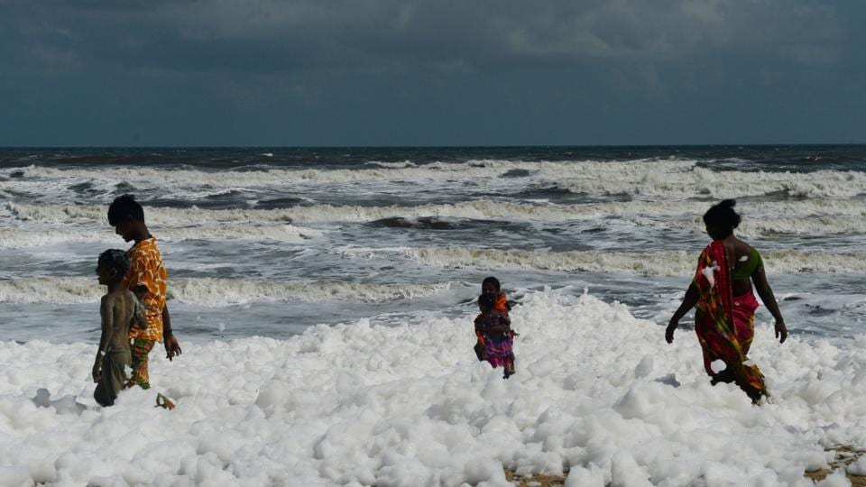 People are seen walking on foam that has formed due to increased pollution, in Chennai, Tamil Nadu. (Arun Sankar / AFP)