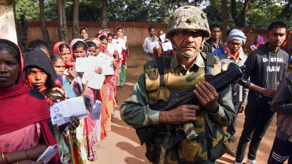 A  paramilitary trooper keeps vigil as people wait in queues to cast their votes at a polling station during the first phase of Jharkhand Assembly elections in Maoist-affected Latehar district  on Saturday.