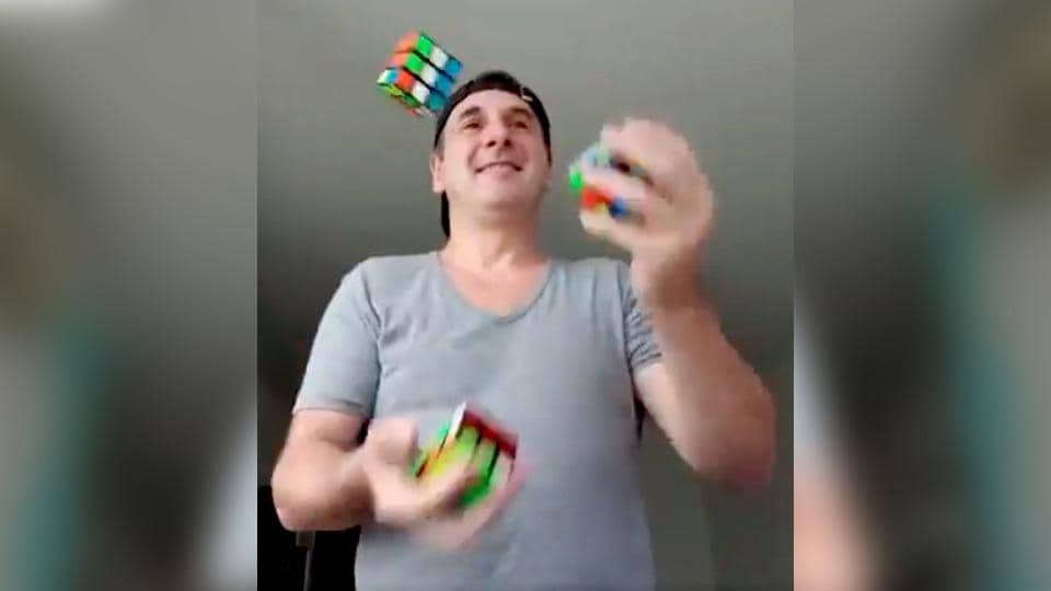 Image shows the man juggling 3 Rubik's cubes.