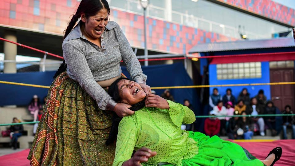 """Ana Luisa Yujra (L), aka """"Jhenifer Two Faces"""" and Lidia Flores, aka """"Dina, The Queen of the Ring"""", members of the Fighting Cholitas, fight at Sharks of the Ring wrestling club in El Alto, Bolivia. The crowd of elderly men, young women and parents with small children heckle and hurled insults as the wrestlers, wearing traditional """"pollera"""" skirts and long braids, put on a chaotic show that often spills outside the ring. (Ronaldo Schemidt / AFP)"""