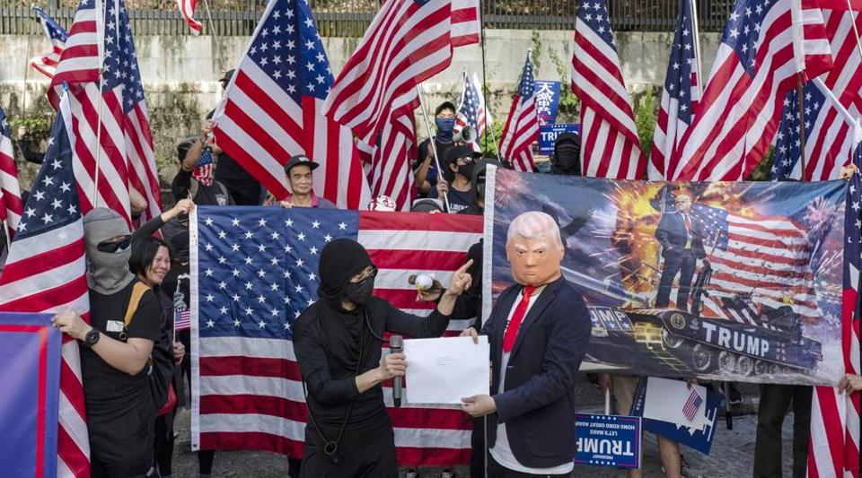 A demonstrator wearing a mask featuring U.S President Donald Trump holds a letter during a protest in the Central district of Hong Kong, China, on Sunday, Dec. 1, 2019. Thousands of protesters on Sunday marched to the U.S. consulate in a rally to express gratitude after PresidentDonald Trumpsigned legislation last week expressing support for the demonstrators.
