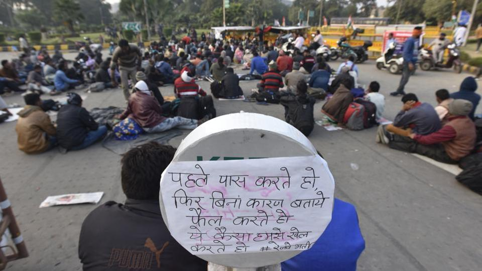 A placard is seen as differently-abled people hold a sit-in protest for the fifth consecutive day against the irregularities in the exam results for railways, at Mandi House circle in New Delhi. (Sonu Mehta/HT Photo)