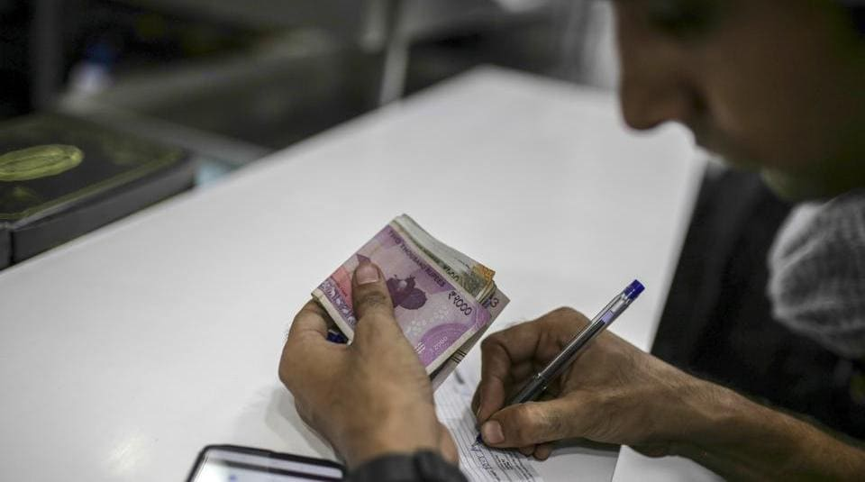 An employee holds Indian rupee banknotes while writing on a notepad n in Mumbai. The tax collection in August  was Rs 98,202 crore.