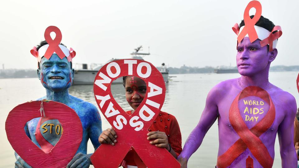 Thalassaemia and AIDS Prevention Society activists paint their bodies to raise awareness about the stigma faced by HIV positive individuals on the eve of World AIDS Day, at Baje Kadamtala Ghat (Babughat), beside river Hooghly, in Kolkata.