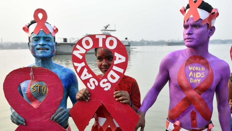 Thalassaemia and AIDS Prevention Society activists paint their bodies to raise awareness about AIDS and the stigma faced by HIV positive individuals on the eve of World AIDS Day, at Baje Kadamtala Ghat (Babughat), beside river Hooghly, in Kolkata, West Bengal. (Samir Jana / HT Photo)