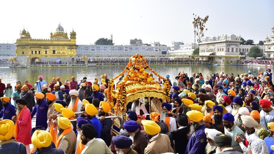 Devotees carry Sri Guru Granth Sahib Ji, the holy book of the Sikhs, in a special golden palanquin as they circumambulate the holy pond during a religious procession on the eve of the martyrdom day of Guru Tegh Bahadur, the ninth Sikh Guru, at Golden Temple, in Amritsar, Punjab. (Sameer Sehgal / HT Photo)