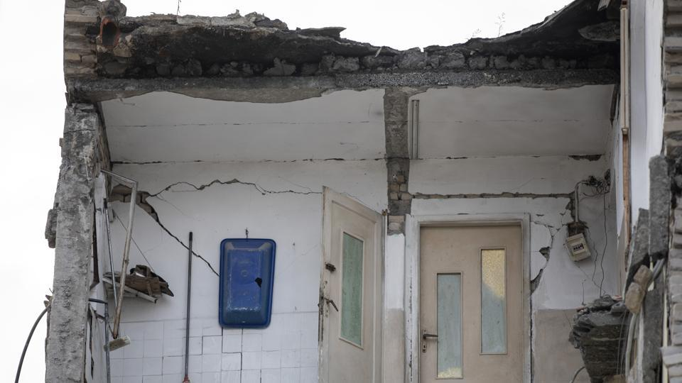 A part of a collapsed building stands in Thumane. Many buildings only partially collapsed, left gaping holes where walls and floors should be, bedroom doors opening into the void, bathroom fixtures dangling from walls in a stark reminder of the powerful and destructive force of nature. (Petros Giannakouris / AP)