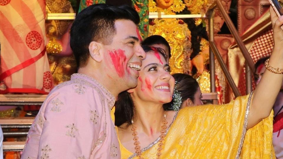 Filmmaker Karan Johar and actress Kajol pose for selfies during Vijaya Dashami celebrations.