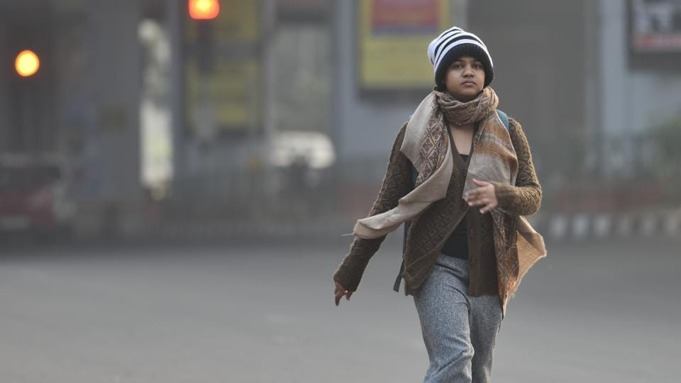 A girl is seen in warm clothes on a winter morning, at Karol Bagh, in New Delhi.