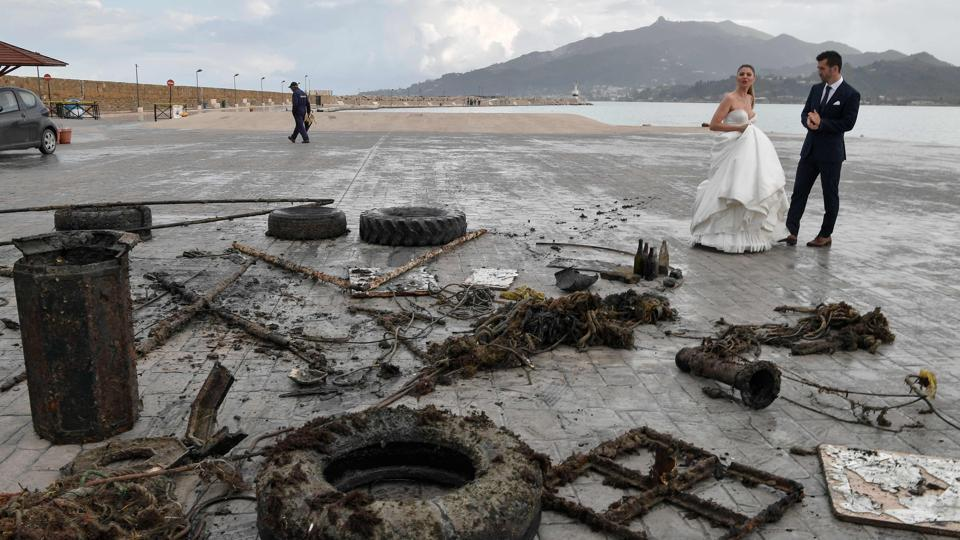 A newly-wed couple looks at rubbish collected from the sea by volunteers. George Triantafyllou, the HCMR's head of research, says the institute is coordinating a European project, Claim, across 13 EU countries in addition to Tunisia and Lebanon to eliminate microplastics. The project includes developing photocatalytic technology to accelerate the degradation of microplastics in seas and rivers, he noted. (Louisa Gouliamaki / AFP)