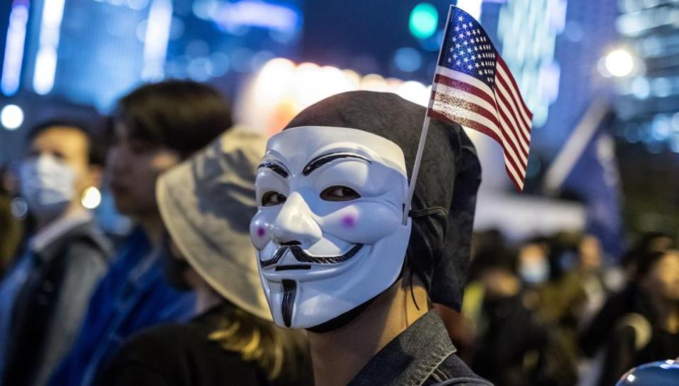 A demonstrator wears an anonymous mask, also known as a Guy Fawkes mask, and an American flag during the Thanksgiving Day Assembly for Hong Kong Human Rights and Democracy Act