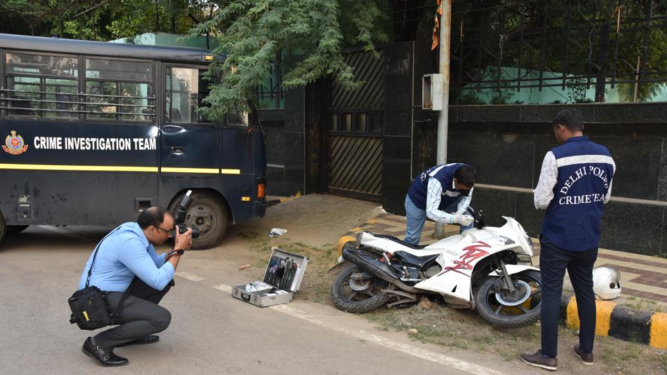 A crime photographer is seen at work, in New Delhi. A team of policemen were busy investigating the vehicle when a tall man, dressed in formals arrived, cameras slung from his shoulders. He cautiously took his position, aimed at the vehicle and clicked away. He is part of the Delhi Police's 60-member crime-scene photographers' team that photographs everything from the untouched crime spot to important objects and documents associated with a crime. (HTPhoto)