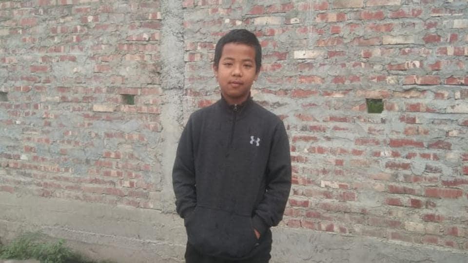 Isaac standing in front of his village school in Manipur's Churachandpur district.