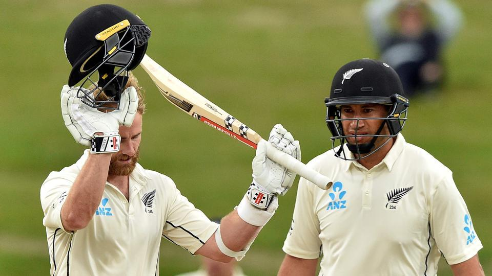 New Zealand's captain Kane Williamson (L) celebrates reaching his century (100 runs) with a teammate Ross Taylor.