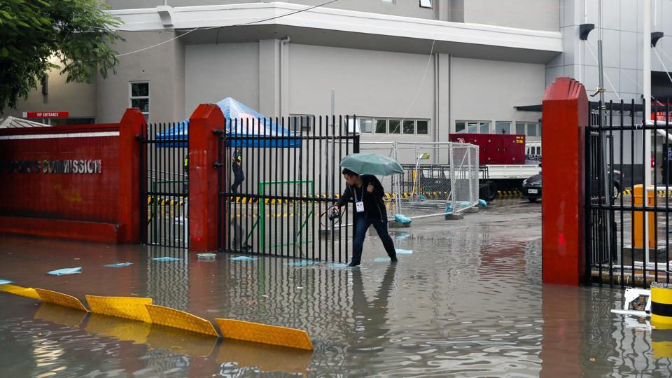 A man walks on the flooded entrance of the Rizal Memorial Stadium, one of the venues for Southeast Asian Games 2019. Kammuri has already snarled some plans for the SEA Games, which opened Saturday and are set to run through December 11 in and around Manila. The typhoon forced organisers to reschedule about half of the events set for Tuesday, but they pledged the competition would finish on time. (Eloisa Lopez / REUTERS)