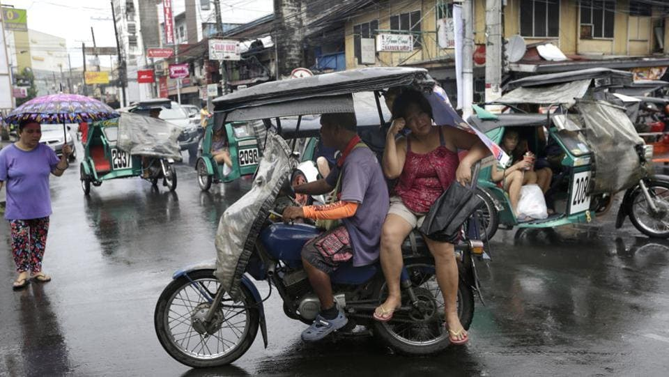 A passenger rides on a three-wheeled cycle during a rain caused by Typhoon Kammuri in Subic. The Philippines is battered by about 20 typhoons and tropical storms each year and has frequent earthquakes and volcanic eruptions, making the archipelago of more than 100 million people one of the world's most disaster-prone nations. (Tayan Syuflana / AP)