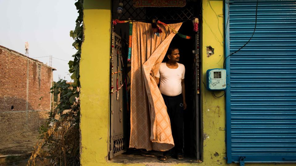 Vinod Kumar Sharma, 44, a visually impaired person stands at the entrance of his home in Asaoti, Haryana. Tapping his white cane, Vinod Kumar Sharma spends four hours a day running the gauntlet of crowded trains and New Delhi's congested, potholed and often pavement-less roads. (Xavier Galiana / AFP)