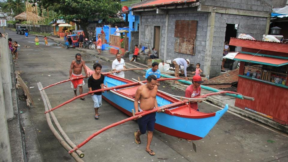 Residents carry to safety a wooden boat in Legaspi City. Government offices and schools were closed in affected areas and utilities firms appealed for patience ahead of anticipated power outages. The coastguard halted commercial sea travel in affected areas stranding more than 6,000 travellers along with thousands of cargo ships and smaller watercraft in the archipelago nation. (Razvale Sayat / AFP)