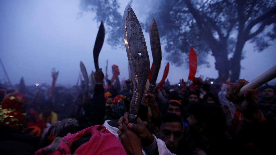 """Devotees raise their sacrificial blades as the sacrificial ceremony of the """"Gadhimai Mela"""" festival begins at Bariyarpur, Nepal. The five-yearly festival, believed to be the world's biggest animal sacrifice at one place, began on Tuesday in the presence of a huge number of pilgrims from India, amid protests by animal activists. Though the month-long festival started on November 17, the main sacrifice days were on December 3 and 4. (Navesh Chitrakar / REUTERS)"""