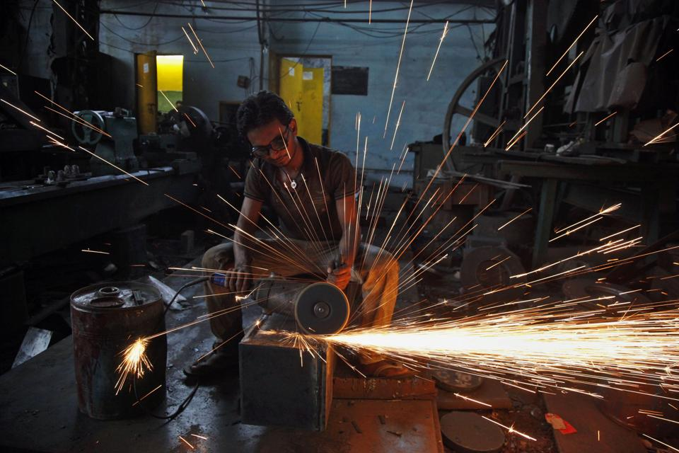 In this April 15, 2015, file photo, a man uses a metal grinder at a factory in Ahmedabad, India.