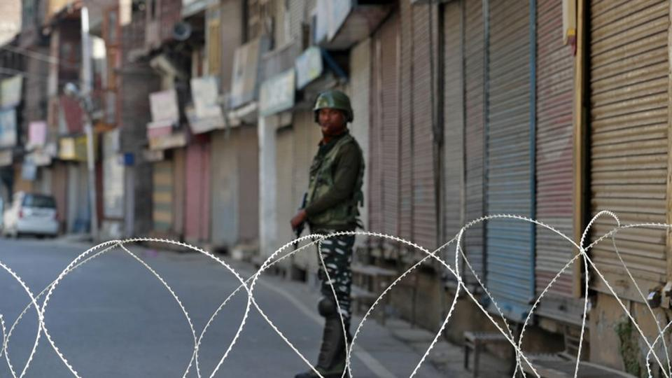 An Indian security force personnel stands guard in front of the closed shops during restrictions following scrapping of the special constitutional status for Kashmir by the Indian government, in Srinagar.