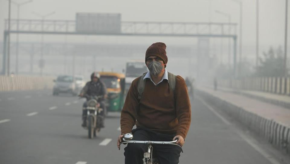 A man rides his bicycle while wearing an anti-pollution mask amid dense fog on a cold winter morning, at NH-24, Mayur Vihar in New Delhi.