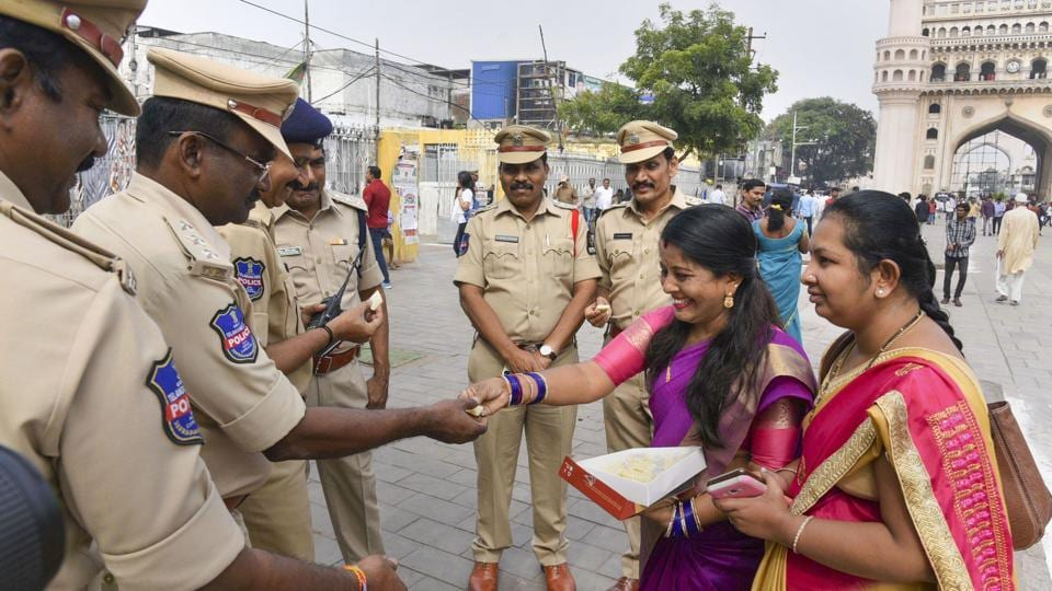 Women offer sweet to policemen as they commend the Hyderabad Police for its strong action against the four accused in the gang rape and murder of a 25-year-old veterinarian, in Hyderabad.