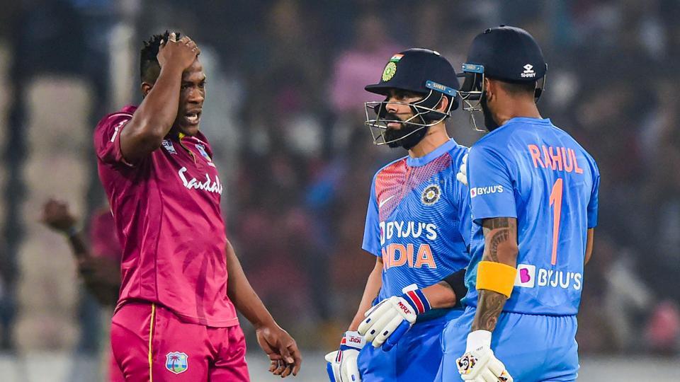 India's skipper Virat Kohli and West Indies bowler talk as batsman KL Rahul looks on.