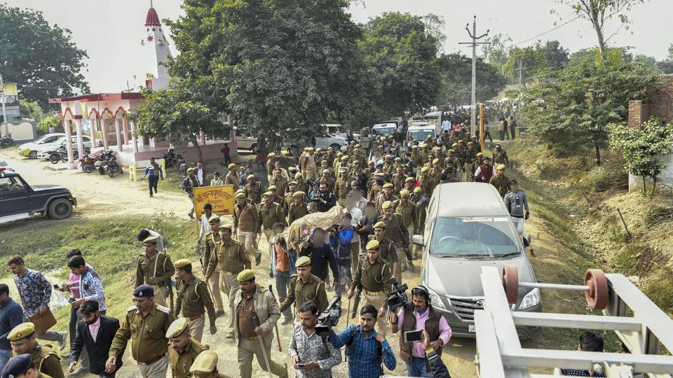 Police personnel march as family members and relatives carry the mortal remains of Unnao rape victim for burial at Unnao, Sunday, Dec. 8, 2019.