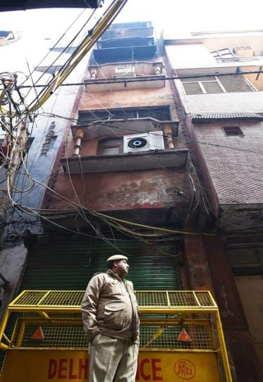 A policeman stands near a building in north Delhi's Anaj Mandi where 43 people were killed in a fire on Sunday.