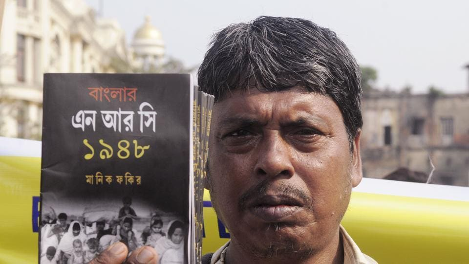 An activist holds a book during the mass rally protest against the National Register of Citizens (NRC), and CAB, in Kolkata.
