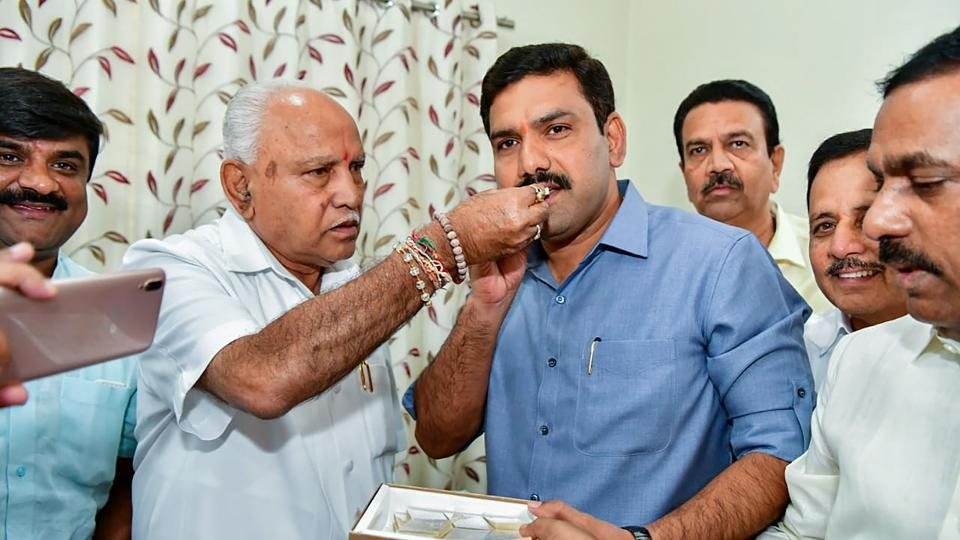 Karnataka Chief Minister BS Yediyurappa offers sweets to his younger son BY Vijayendra after BJP won in 12 out of 15 assembly constituencies in the bypolls in Karnataka.