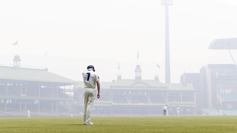 Liam Hatcher of the Blues stands in the outfield amid the smoke haze from bushfires during day 3 of the Sheffield Shield match between New South Wales and Queensland at the SCG in Sydney.