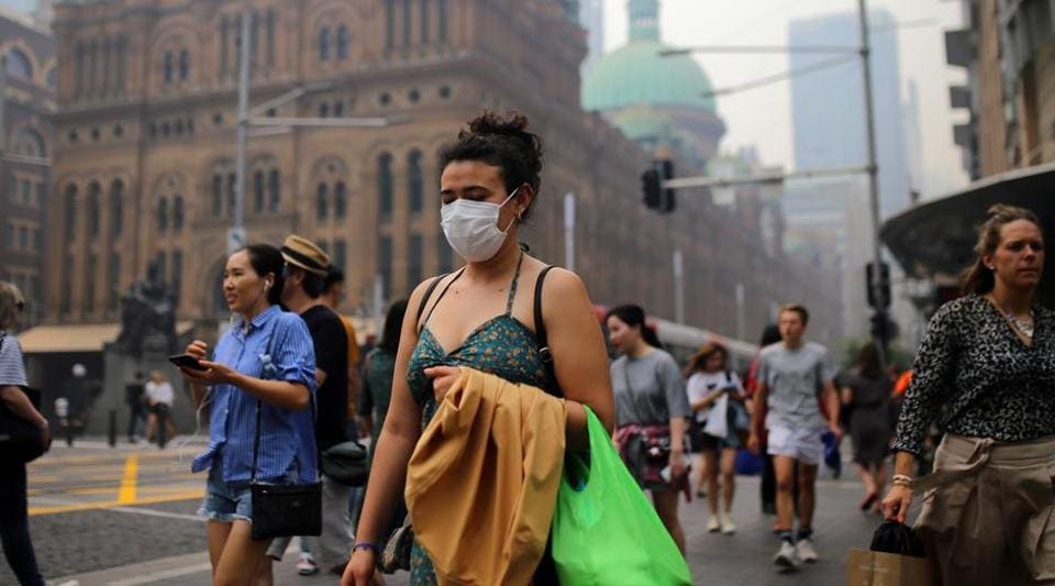Pedestrians are seen wearing masks as smoke haze from bushfires in New South Wales blankets the CBD in Sydney, Australia.