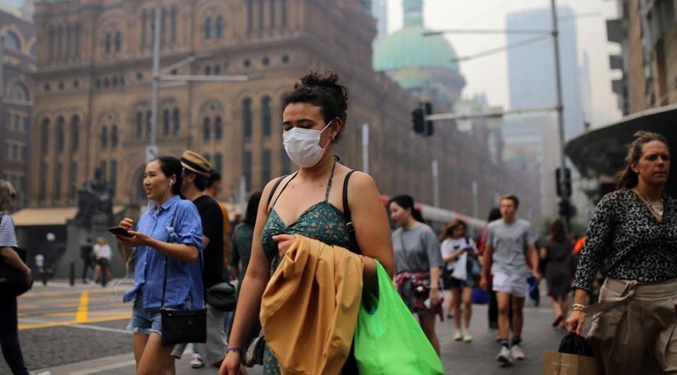 Pedestrians are seen wearing masks as smoke haze from bushfires in New South Wales blankets the CBD in Sydney, Australia.