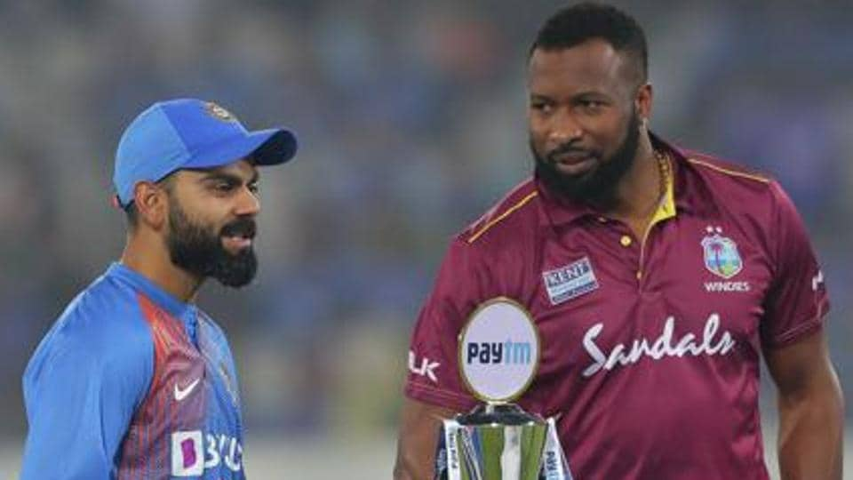India's captain Virat Kohli, left, interacts with West Indies' captain Kieron Pollard as they pose with the series trophy.
