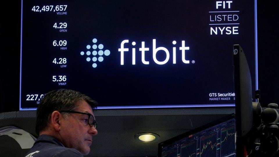 FILE PHOTO: A trader works at his post as the logo for wearable device maker Fitbit Inc. is displayed on a screen on the floor of the New York Stock Exchange (NYSE) as begins public trading in New York, U.S., October 28, 2019. REUTERS/Brendan McDermid