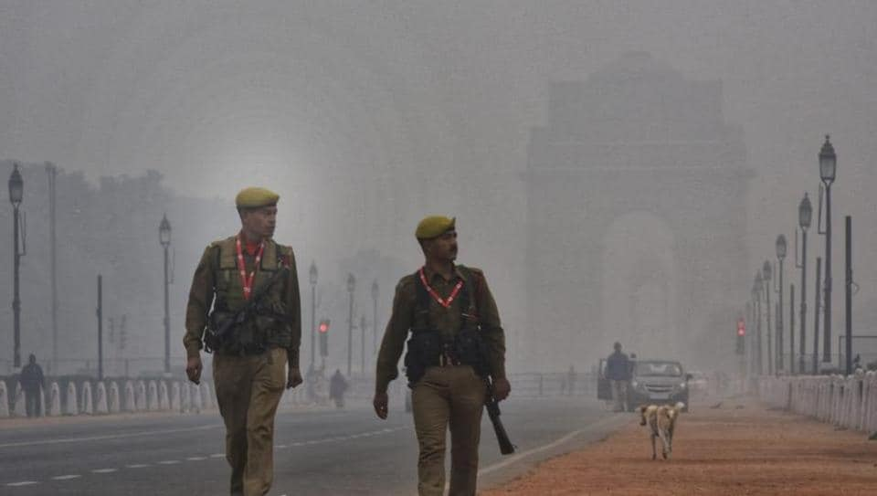 Security personnel walks in thik fog at Rajpath as temperature dips in Delhi.