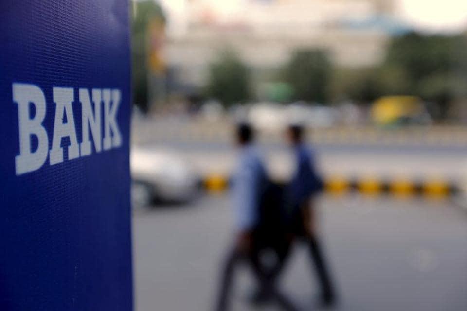 Commuters walk past a bank sign along a road in New Delhi.