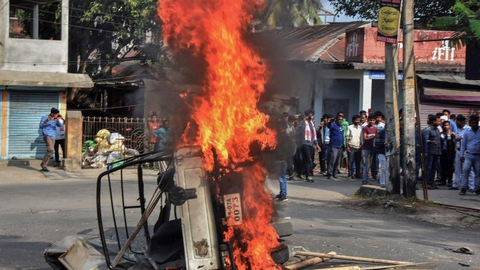 Protestors burn a vehicle to block a road during an agitation against the Citizenship Amendment Bill, in Tezpur, Assam.