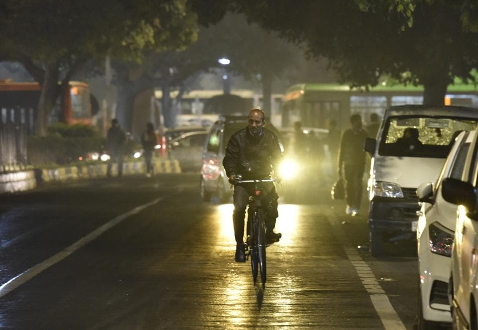 A cyclist out during a light rain shower at Ashoka Road in New Delhi, India on Thursday.