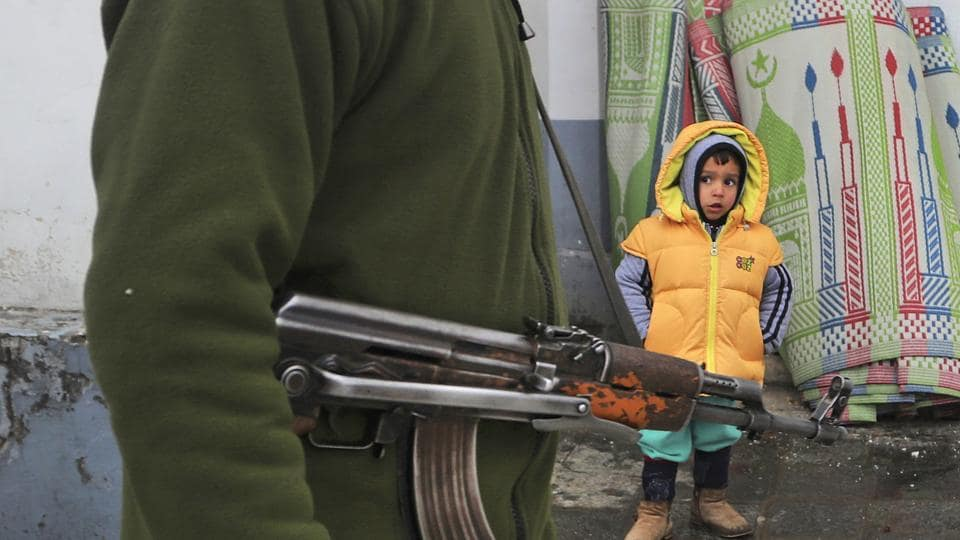 An Indian policeman guards as a Kashmiri child looks on outside the Hazratbal shrine, on the occasion of the Prophet's birth anniversary in Srinagar.