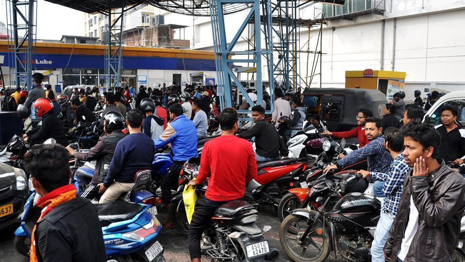 Commuters wait at a petrol pump during curfew relaxation in Guwahati.