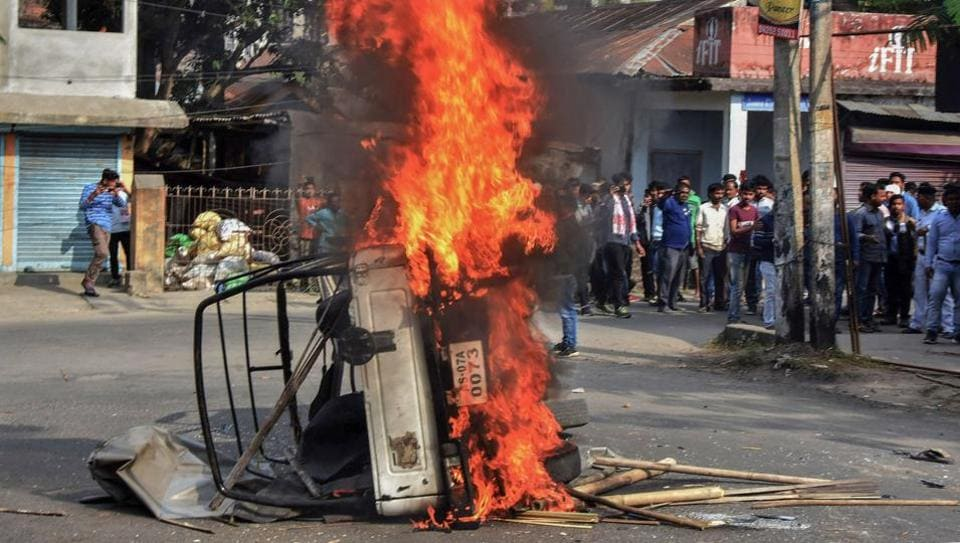 Protestors burn a vehicle to block a road during an agitation against the citizenship law in Assam's Tezpur.