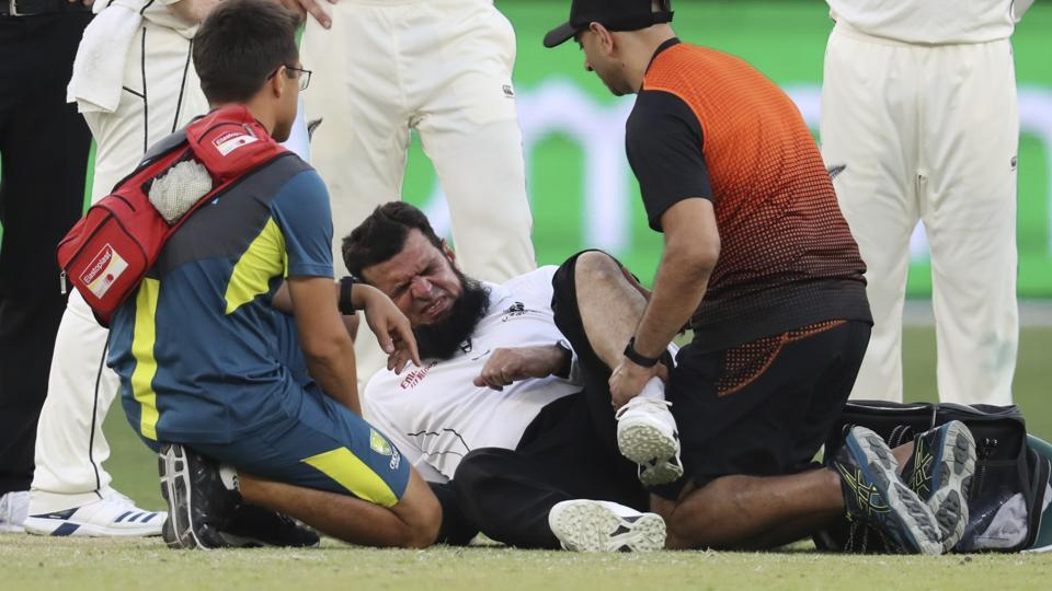 Umpire Aleem Dar is attended to by medical staff.