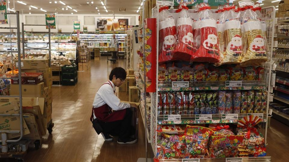 "An employee stocks shelves at a newly opened Aeon supermarket in Namie. The word Fukushima has become globally known, but regrettably the situation in Futaba or (neighboring) Okuma is hardly known,"" Izawa said, noting Futaba's recovery won't be ready by the Olympics. ""But we can still show that a town that was so badly hit has come this far,"" he added. (Jae C. Hong / AP)"