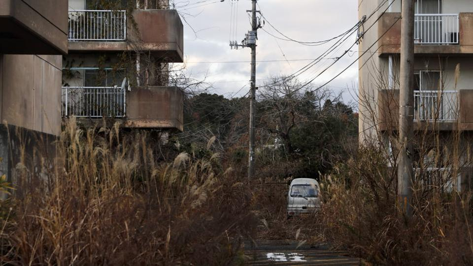 "Weeds grow in an abandoned apartment complex. ""This recovery Olympics is in name only,"" Toshihide Yoshida said. He was forced to abandon Futaba and ended up living near Tokyo. ""The amount of money spent on the Olympics should have been used for real reconstruction."" (Jae C. Hong / AP)"